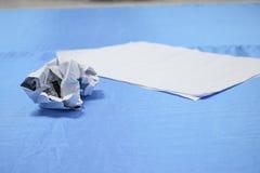 Zerknitterter Papierklumpen und Beschaffenheit auf blauem Tabellenhintergrund Stockfotografie