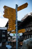 Signage in Zermatt. Zermatt is a ski resort that straddles the border between Switzerland and Italy. Signage to Cities in the far distance stock image