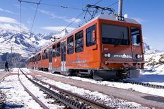 Orange train at Zermatt, Switzerland. Zermatt, Switzerland - August 12, 2017: Orange electric train at the station on the viewpoint to the Matterhorn mountain royalty free stock photography