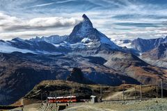 Zermatt Switzerland. Famous electric red tourist train coming do Stock Image