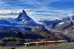 Famous electric red tourist train coming down in Zermatt royalty free stock photography