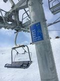 """Funny slogan an a pole of a chair lift """"A bad day of skiing be. Zermatt, Switzerland - March 20, 2018: A funny slogan on a pole of a chair lift in the royalty free stock photos"""