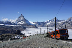 Zermatt, Switzerland - October 8, 2016: The travel train to Gone. Rgrat bahn running through the railway with the beautiful Matterhorn mountain in the background stock photo