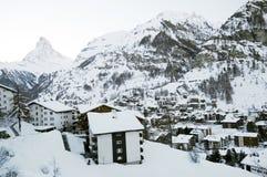 Zermatt village in winter. Snow covered houses in Zermatt village with Matterhorn mountain and Pennine Alps in background, Valais, Switzerland stock photo