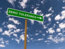 Zero tolerance. In block text with directional arrow on green traffic sign against blue skies with clouds stock images