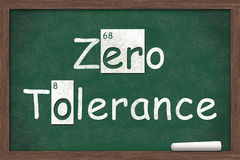 Zero Tolerance. Written on a chalkboard with letters from the periodic table and a piece of white chalk royalty free stock image