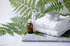 Zero waste bathroom accessories, natural sisal brush, aroma oil, metal jar, cotton towel, essential oil on marble plate, minimal. Eco-friendly background stock photography