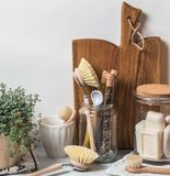 Zero waste concept. Eco-friendly kitchen set. Brushes, soap in jar, spices in glass tubes and plant in wood flowerpot. Copy space royalty free stock images