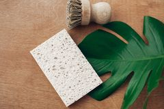 Zero waste concept, flat lay. Reusable natural cellulose sponge and eco wooden brush on wooden background with green monstera leaf. Ban single use plastic stock photography