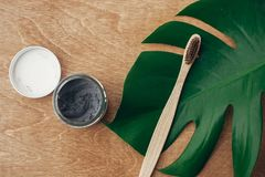 Zero waste concept. Natural toothpaste activated charcoal in glass jar and bamboo toothbrush on wooden background with green. Monstera leaf. Plastic free stock photos