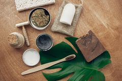 Zero waste flat lay. Natural soap, solid shampoo, metal razor, crystal deodorant, charcoal toothpaste, sponge, bamboo toothbrush,. Ubtan on wood with green stock photo