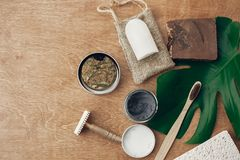 Zero waste flat lay. Natural soap, solid shampoo, metal razor, crystal deodorant, charcoal toothpaste, sponge, bamboo toothbrush. On wood with green monstera stock photos