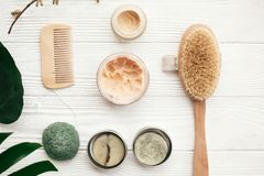 Zero waste flat lay. Natural solid shampoo, wooden brush, deodo. Rant cream, scrub and konjaku sponge on white wood with green monstera leaves. Eco products stock photos