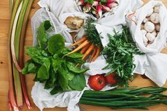 Zero waste grocery shopping concept,flat lay. Reusable eco friendly bags with fresh vegetables carrots,tomatoes, spinach,arugula,. Mushrooms,rhubarb,onions on royalty free stock images