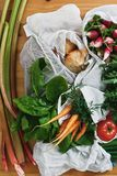 Zero waste grocery shopping concept,flat lay. Reusable eco friendly bags with fresh vegetables carrots,tomatoes, spinach,arugula,. Mushrooms,rhubarb,onions on royalty free stock photography
