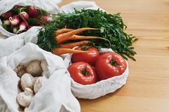 Zero waste grocery shopping concept. Reusable eco cotton bags with fresh vegetables carrots,tomatoes, arugula, mushrooms from. Market on wooden table. ban stock images