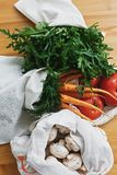 Zero waste grocery shopping concept. Reusable eco cotton bags with fresh vegetables carrots,tomatoes, arugula, mushrooms from. Market on wooden table. ban royalty free stock photo