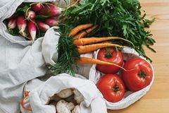 Zero waste grocery shopping concept. Reusable eco cotton bags with fresh vegetables carrots,tomatoes, arugula, mushrooms from. Market on wooden table. ban royalty free stock photography