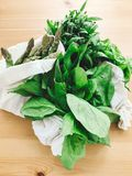 Zero waste grocery shopping concept. Reusable eco friendly bags with fresh asparagus, arugula,spinach,basil on wooden table, top. View. Ban plastic. Choose stock photography