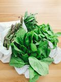 Zero waste grocery shopping concept. Reusable eco friendly bags with fresh asparagus, arugula,spinach,basil on wooden table, top. View. Ban plastic. Choose stock photos