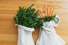 Zero waste grocery shopping concept. Reusable eco friendly bags with fresh vegetables carrots, arugula, on wooden table, flat lay. Ban plastic. Sustainable stock image