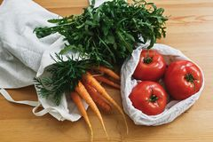 Zero waste grocery shopping concept. Reusable eco friendly bags with fresh vegetables carrots,tomatoes, arugula,  from market on. Wooden table. ban plastic stock images