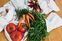 Zero waste grocery shopping concept. Reusable eco friendly bags with fresh vegetables carrots,tomatoes, arugula, mushrooms from. Market on wooden table. ban royalty free stock images