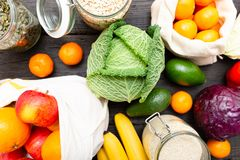 Zero waste grocery shopping. Package-free food on dark wooden table with texture. Fresh vegetables and fruits in Eco cotton bags. royalty free stock photography