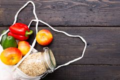 Zero waste grocery shopping. Package-free food on dark wooden table with texture. Fresh vegetables and fruits in Eco cotton bags. stock image
