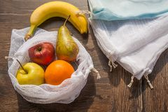 Zero waste recycled textile produce shopping bag. Zero waste, plastic free recycled textile produce bag for carrying fruit apple, orange, pear and a banana or royalty free stock images