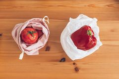 Zero Waste shopping, flat lay. Fresh groceries in reusable eco bags and vegetables in plastic polyethylene bag on wooden table. stock photo
