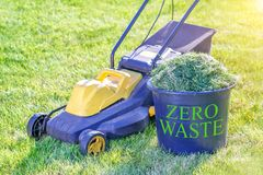 Zero waste theme. Container with fresh grass for compost and lawn mower stock photos
