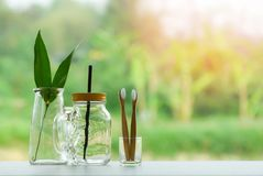 Zero waste use less plastic concept / eco green leaf in water glass jar with straw pitcher vase and bamboo toothbrush royalty free stock photos