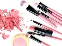 Zerquetscht bilden Sie Pulver- und Lippenstiftproben mit Bürsten auf weißem Hintergrund Lizenzfreies Stockfoto