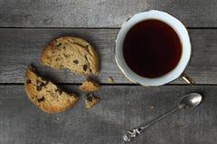 Zerquetschte Plätzchen mit Tee auf einem hölzernen Hintergrund Lizenzfreie Stockfotografie