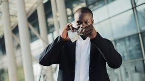 Zerreißende Dollarscheine des Afroamerikanergeschäftsmannes Er stehend nahe Bürogebäude Geldentwertung, Börse stock video footage