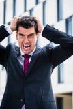 Zerreißendes Haar des verärgerten Mannes in der Verzweiflung Stockbild