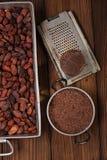 Zerriebene dunkle Schokolade im Zinn mit Kakaobohnen und festem Stück herein stockbilder