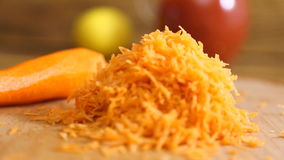 Zerriebene Karotten auf einem hölzernen Brett stock video footage