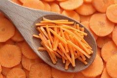 Zerriebene Karotten in einem hölzernen Löffel Lizenzfreies Stockfoto