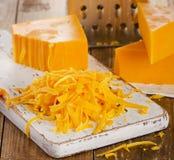 Zerriebener Cheddar-Käse auf hölzernem Schneidebrett Stockfoto