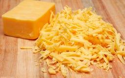Zerriebener Cheddarkäsekäse auf hölzernem Vorstand Stockfoto