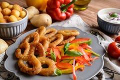 Zerschlagen Sie gebratene Kalmarringe mit Kartoffelkroketten und Pfeffersalat Stockfoto