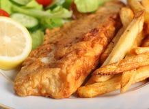 Zerschlagene Fische mit Chips und Salat Stockbilder