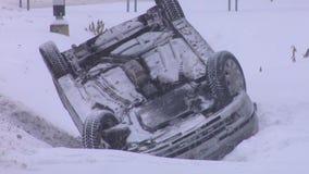 Zerschmettertes Auto umgedreht auf dem Dach nach einem Unfall auf Winter-Straße mit Schnee stock video