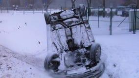 Zerschmettertes Auto umgedreht auf dem Dach nach einem Unfall auf Winter-Straße mit Schnee stock footage