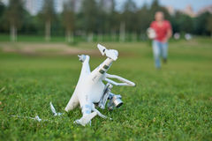 Zerschmettertes quadrocopter im Park Propellerschaden Betreiber, der auf dem Hintergrund läuft Stockbilder