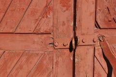 Zerstörte die alte rote Tür Stockfotografie