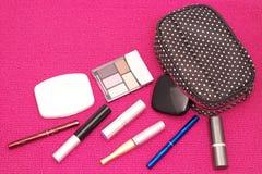Zerstreuen von Kosmetik mit einer Kosmetiktasche auf einem rosa Hintergrund Stockbild