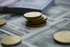 Zerstreute Banknoten von 100 US-Dollars und von Euromünzen Stockbilder